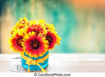 Fresh flowers in vase on wooden table. Vintage background.