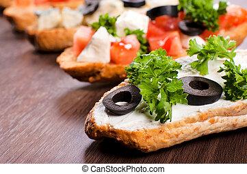 Fresh bruchettas with olive on wooden tabl. Slective focus on the first bruschtta