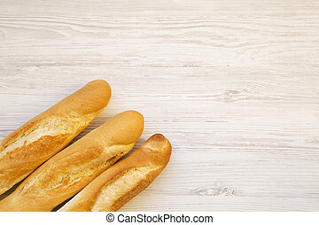Fresh french baguettes on white wooden background, top view. Copy space.
