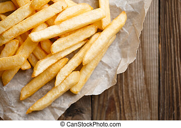 Fresh french fries on wooden background