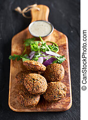 fresh fried vegan falafel with dipping suace on wooden bread board