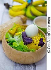Fresh fruit and fresh vegetable salad with cream salad in wooden bowl