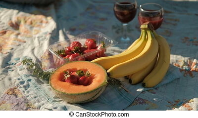 Fresh fruit and two glasses with red wine lie on the beach.