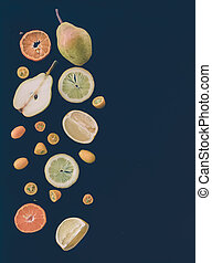 Fresh fruit andcitrus mix on black: pieces of pear,...