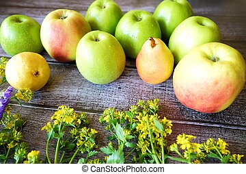 Fresh fruit apples and pears on a brown background