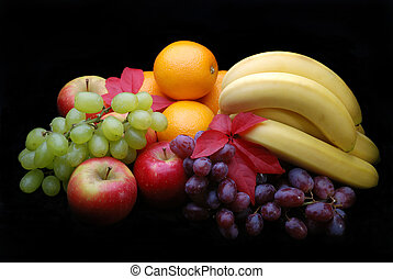 Apples, oranges, grapes and bannanas on a black background