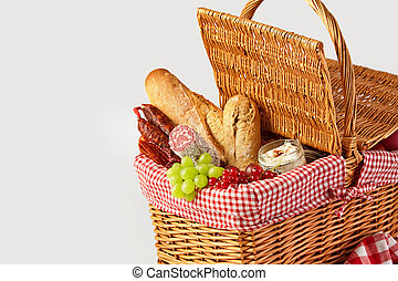 Fresh fruit, bread and cheese in a picnic basket