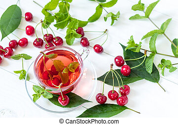 Fresh fruit cherry drink in transparent glass cup surrounded by cherries on the white wooden background. Top view