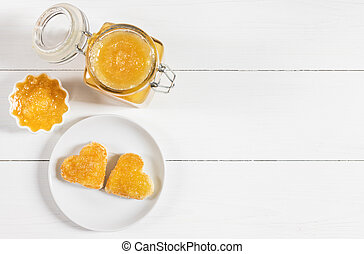 Fresh fruit jam on a white wooden background. Toast hearts in a plate. Yellow confiture. Copy space, top view, flat lay.