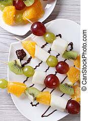 Fresh fruit on skewers with chocolate sauce vertical top view