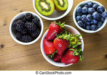 Organic fresh fruit in round bowls on wood table.