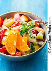 Fresh fruit salad full of vitamins for summer on blue background