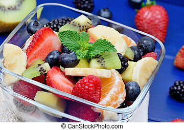 Fresh fruit salad in a bowl on blue wooden table
