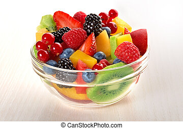fresh fruit salad in glass bowl isolated on beige wood table