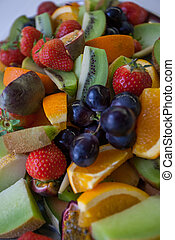 Fresh fruit salad, including sliced strawberries, blueberries, grapes, cantaloupe, and honeydew melon, for themes of health food, nutrition, freshness