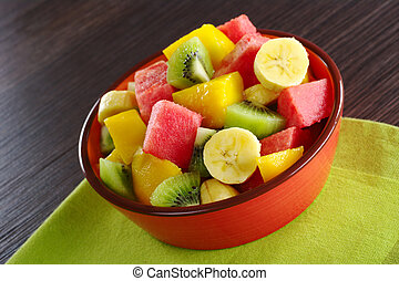 Fresh fruit salad made of banana, kiwi, watermelon and mango pieces in orange bowl (Selective Focus, Focus on the front of the bowl and the fruits in the front)