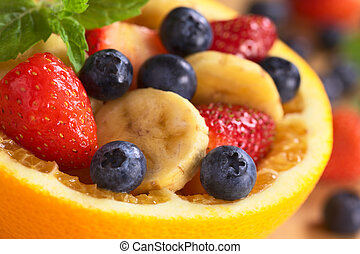 Fresh fruit salad made of banana, strawberries and blueberries in a bowl made of a half orange garnished with a mint leaf (Very Shallow depth of Field, Focus on the blueberry in the right bottom edge)