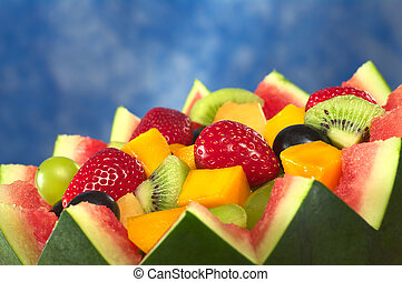 Fresh fruit salad of mango, strawberry, kiwi and grapes in a bowl from watermelon in front of blue background (Selective Focus, Focus in the middle of the fruit salad)