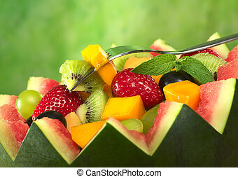 Fresh fruit salad (strawberry, kiwi, mango, grape) in melon bowl with kiwi and mango on fork and a mint leaf as garnish in front of green background (Selective Focus, Focus on the fruit on the fork an