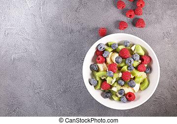 fresh fruit salad with banana, blueberry, kiwi and raspberry