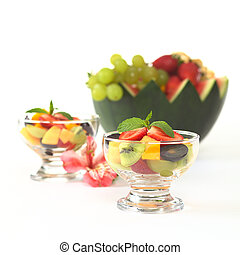 Fresh fruit salad with strawberry, kiwi, mango and grapes in glass bowl garnished with mint leaf with Inca Lily and a watermelon bowl full of fruits in the back (Selective Focus, Focus on the mint lea