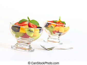 Fresh fruit salad with strawberry, kiwi, mango and grapes in glass bowl garnished with mint leaf (Selective Focus, Focus on the mint leaf in the first bowl)