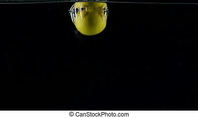 Fresh fruit yellow lemon falls into clear water with splash