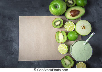Fresh fruits and green smoothie on a blank paper note. Above view with copy space.