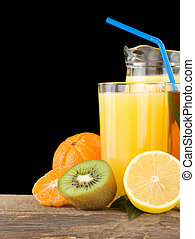 fresh fruits and juice in glass isolated on black