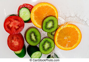 fresh fruits and vegetables in water on a white background