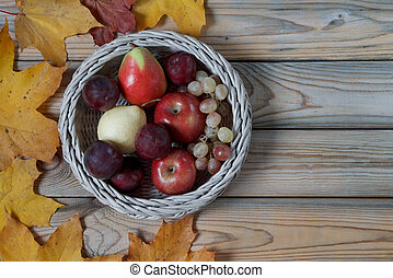 Fresh fruits are lying in a wicker basket. Autumn still life. Copy space for your text.
