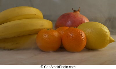 Fresh fruits, bananas, pomegranates, tangerines and lemon are in the kitchen from which blows freshness and coolness, close-up, slow motion