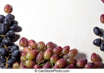Fresh fruits grapes, pear and apple on wooden boards frame background.