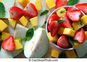 Fresh fruits – guava, mango and strawberry with leaves of mint on the wooden background.