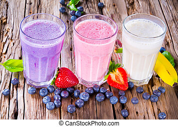 Fresh milk, strawberry, blueberry and banana drinks on wodeen table, assorted protein cocktails with fruits.