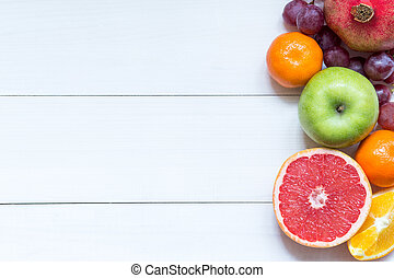 Fresh fruits on wooden boards frame background