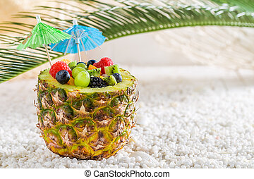 Fresh fruits salad in pineapple with cocktail umbrellas on beach