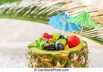 Fresh fruits salad in pineapple with cocktail umbrellas