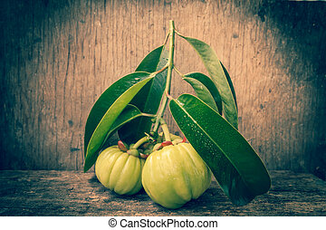 Still life garcinia atroviridis fresh fruit on old wood background. Thai herb and sour flavor lots of vitamin C. Diet health care weight reduction. Vignette and low key picture style.