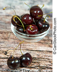Fresh garden cherry in bowl on wooden background