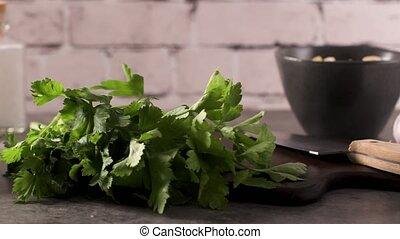 Fresh garden herbs on kitchen countertop. Parsley, garlic,...