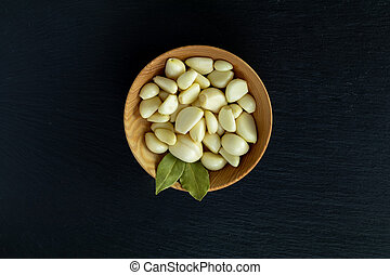 Fresh garlic heads, cloves set on a black stone surface