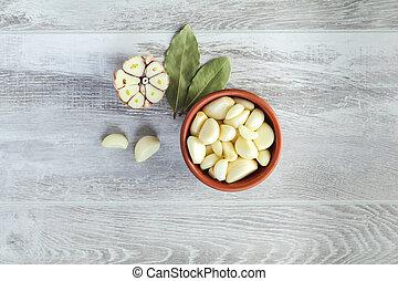 Fresh garlic heads, cloves set on a light gray wooden surface