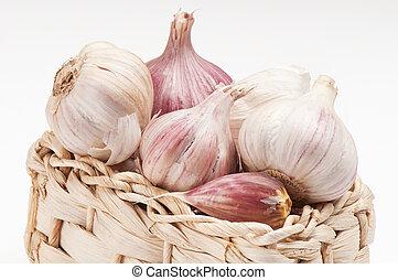 Fresh garlic in a basket on a white background