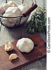 Fresh garlic on cutting board on vintage wooden background