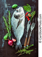Fresh Gilt-head bream with spices and seasoning on slate...