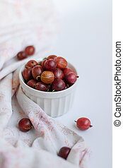 Fresh gooseberries in a ceramic bowl on white table. View from above.
