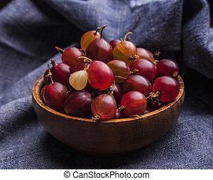 Fresh gooseberries in a wooden bowl