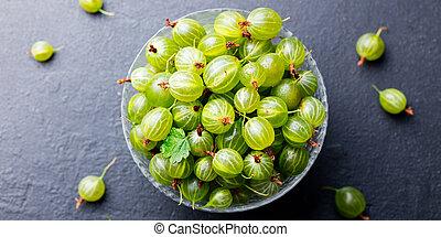 Fresh gooseberries in glass bowl. Top view.