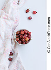 Fresh gooseberry berry in a bowl on white background. top view